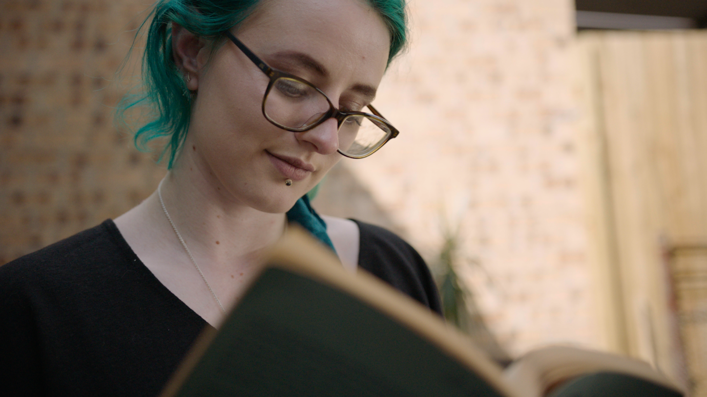 Person with green hair and glasses, sitting in front of a wall and reading a book.