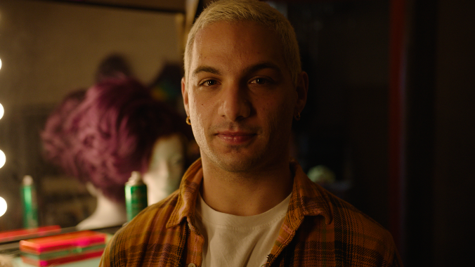 Man with short bleached hair and a check shirt sitting in front of a dressing table mirror.