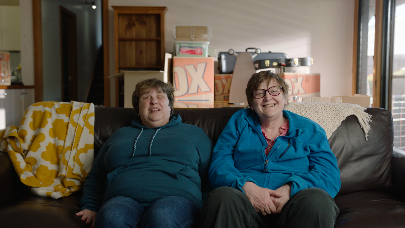 Two women wearing hoodies and trousers sitting on a sofa with moving boxes in the background.