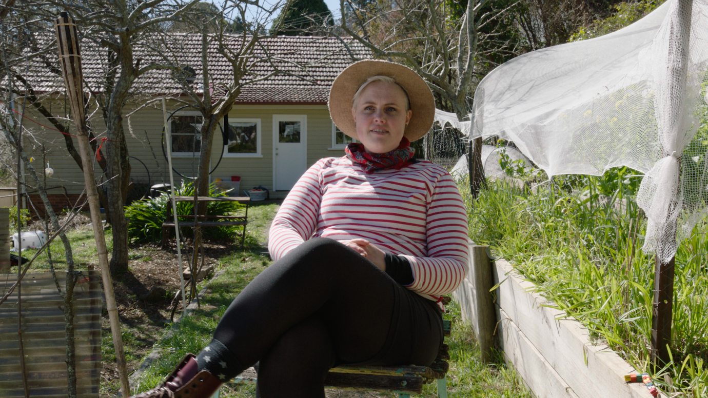 Woman in a straw hat and striped top sitting on a chair in a garden with trees and a single story house in the background.