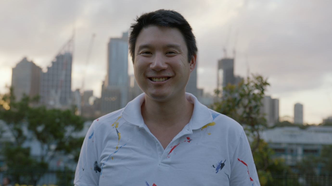 Man in a white polo shirt standing outside with trees in the background and the Sydney skyline in the distance.