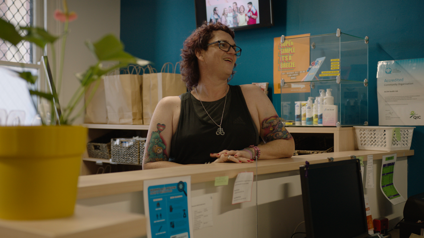 Woman wearing a black sleeveless top, glasses and pendant stands smiling at a reception desk.